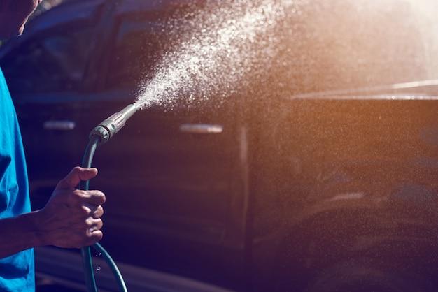 Main flou tenant le tuyau de lavage de voiture