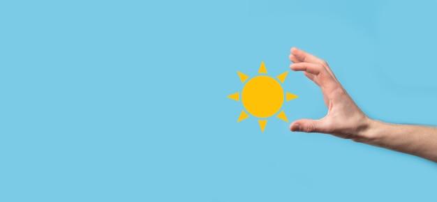 La main sur fond bleu contient le symbole de l'icône du soleil. source d'électricité durable, concept d'alimentation électrique. approche technologique respectueuse de l'environnement.