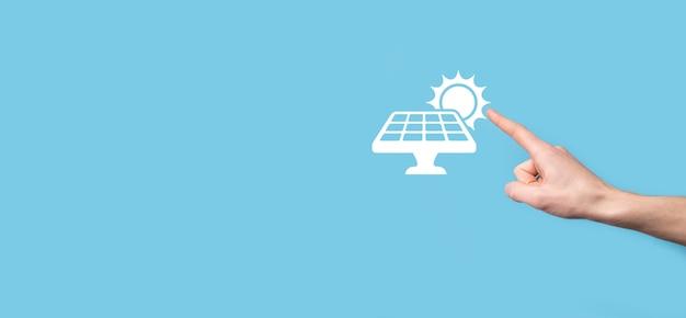 La main sur fond bleu tient le symbole de l'icône des panneaux solaires. énergie renouvelable, concept de station de panneaux solaires, électricité verte.