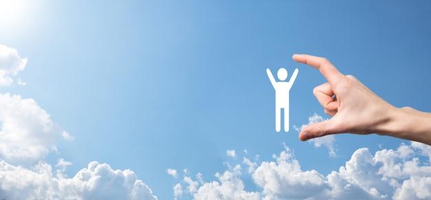 La main sur fond de ciel détient l'icône humaine