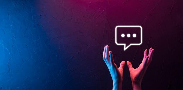Main Sur Fond Néon Tenant Une Icône De Message, Signe De Notification De Conversation De Bulle Dans Ses Mains. Icône De Chat, Icône Sms, Icône De Commentaires, Bulles De Dialogue Photo Premium