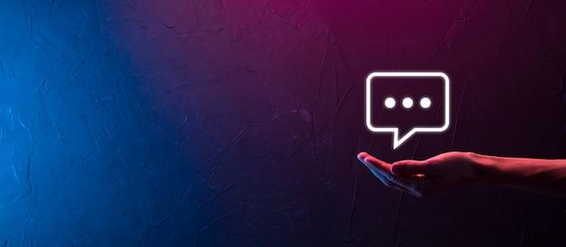 Main sur fond néon tenant une icône de message, signe de notification de conversation de bulle dans ses mains. icône de chat, icône sms, icône de commentaires, bulles de dialogue