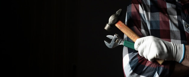Main forte de bricoleur dans les gants agrandi avec des outils de marteau et de clé. bannière avec espace de copie.