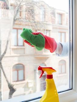 Main avec un gant en caoutchouc nettoyant la fenêtre