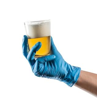 Main avec gant en latex bleu tenant un verre de bière