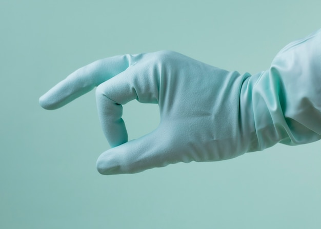 Main avec un gant médical sur fond vert