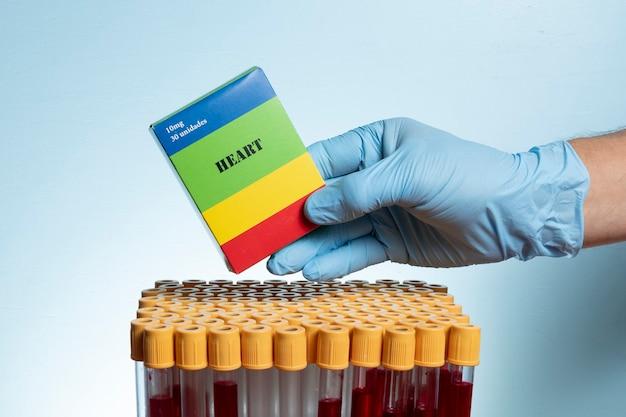 Main avec gant de protection en nitrile tenant la boîte de médicaments avec des tubes de prélèvement sanguin.