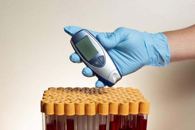 Main avec gant de protection en nitrile tenant un glucomètre avec des tubes de prélèvement sanguin.