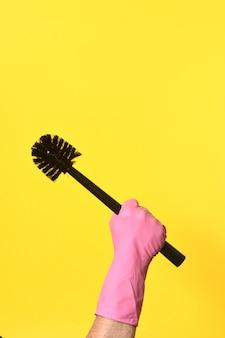 Main avec gant tenant le pinceau sur fond jaune