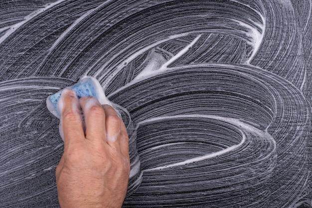 La main avec un gant de toilette bleu lave un tableau noir. texture mousse abstraite sur fond noir. bulles de mousse de savon abstrait fond sombre, vue de dessus