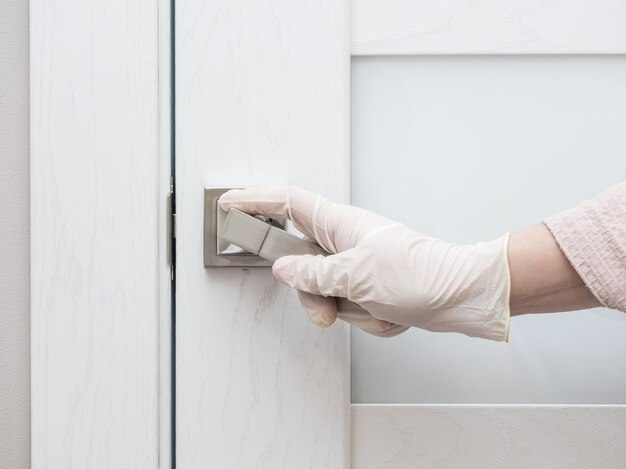Une main gantée de caoutchouc tient la poignée de la porte d'entrée.