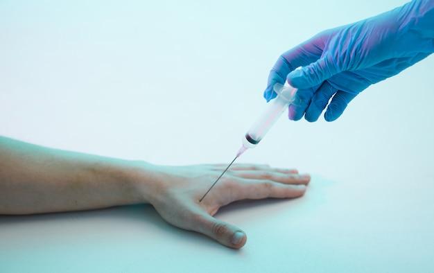 La main gantée du médecin fait une injection de seringue dans la main d'un gros plan d'un patient masculin.