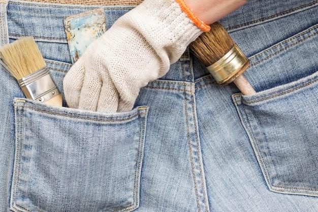 La main gantée prend l'outil de réparation de la poche du jean. outils anciens et poussiéreux. fermer