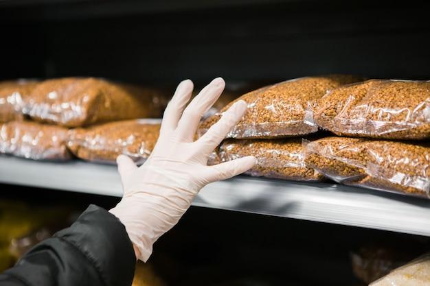 Une main gantée prend un paquet de sarrasin sur une étagère de magasin, la sécurité épidémique