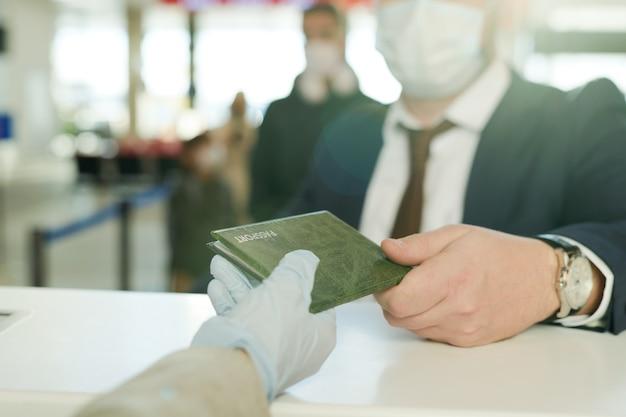 Main gantée d'une réceptionniste qui rend le passeport d'un homme d'affaires élégant au comptoir de la réception après l'enregistrement avant le vol