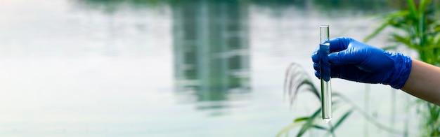 Une main gantée recueille l'eau dans un tube à essai. échantillonnage en eau libre dans un plan d'eau de la ville. scientifique ou biologiste prélevant un échantillon d'eau dans un tube à essai dans le contexte d'un paysage urbain