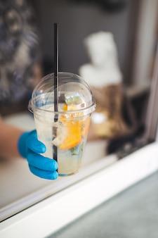 Une main gantée tend une boisson rafraîchissante avec du gingembre et de la glace