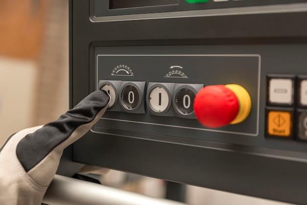 La main avec des gants appuie sur le bouton d'alimentation d'une machine à bois dans une usine en gros plan