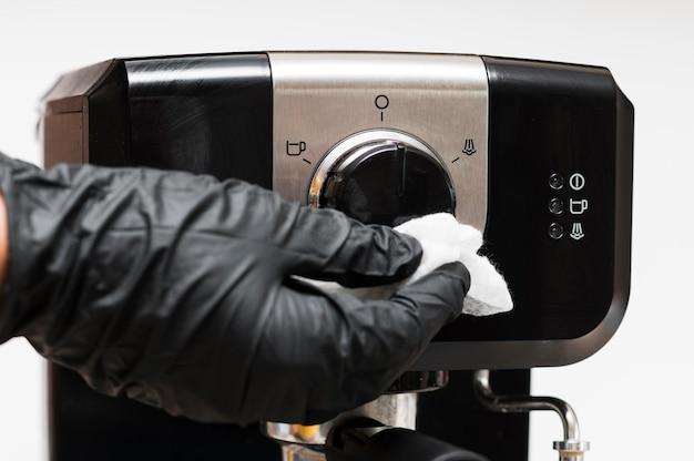 Main avec des gants désinfectant la machine à café instantané