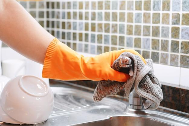 Main avec des gants essuyant un évier en acier inoxydable avec un chiffon