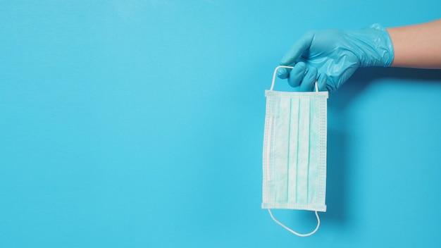 Main avec des gants et tenant un masque facial mis sur fond bleu