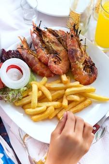 Main garçon mangeant des fruits de mer aux crevettes et pommes de terre frites à la table du dîner par soi-même.