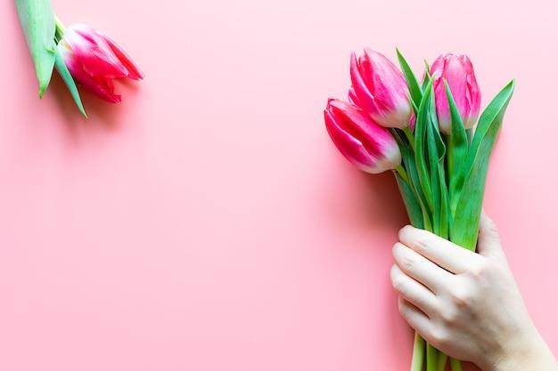 Main de garçon tenant le bouquet de belles tulipes roses sur fond pastel rose