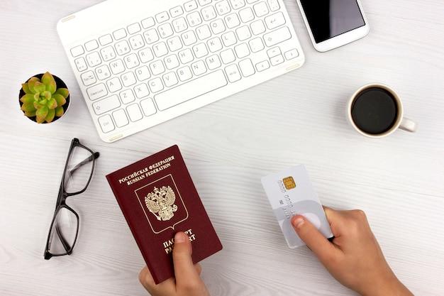 La main garde la carte de crédit pour la réservation en ligne d'un hôtel et d'un billet d'avion