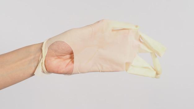Main gauche porter des gants médicaux déchirés ou des gants en caoutchouc qui fuient sur fond blanc.