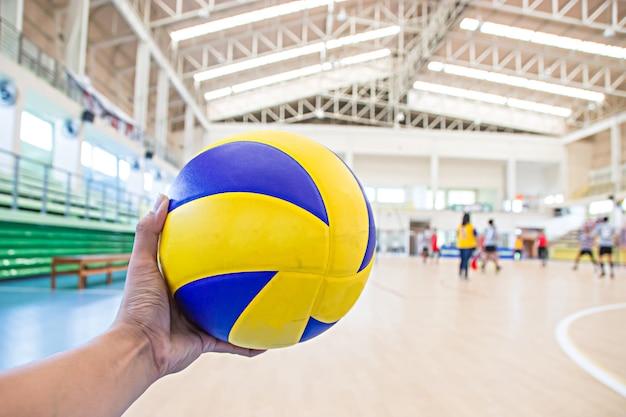 La main gauche tient un ballon de volley