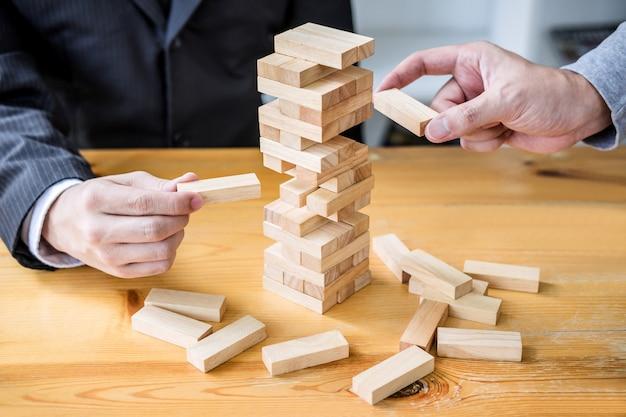 Main de gens d'affaires plaçant et tirant un bloc de bois sur la tour, concept de risque alternatif