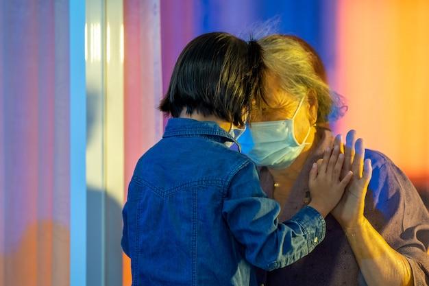 Main de la grand-mère et du petit-enfant sur un avion de fenêtre, protection contre le coronavirus et la pandémie de covid-19, concept de distance sociale.