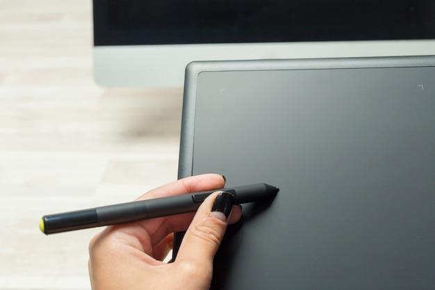 Main de graphiste travaillant avec stilus et tablette