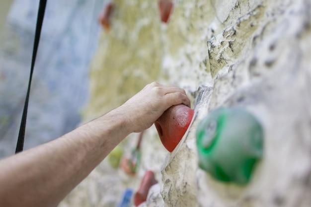 Main grimpant sur un mur artificiel.