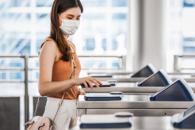 Main en gros plan à l'aide d'un téléphone mobile intelligent d'une jeune passagère asiatique portant un masque chirurgical