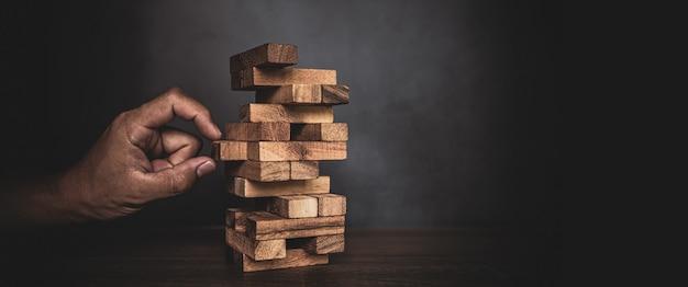 La main en gros plan choisit le bloc boisé empilé dans la tour