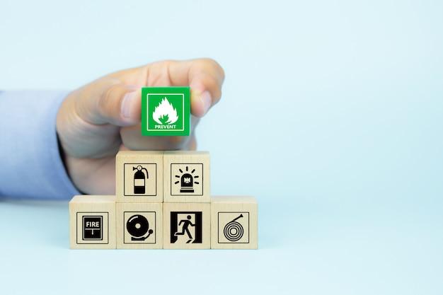La main en gros plan choisit des blocs de bois avec l'icône de prévention des incendies.
