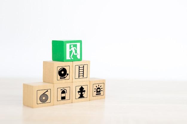 La main en gros plan choisit des blocs de jouets en bois empilés en pyramide avec la sortie de la porte chanter.