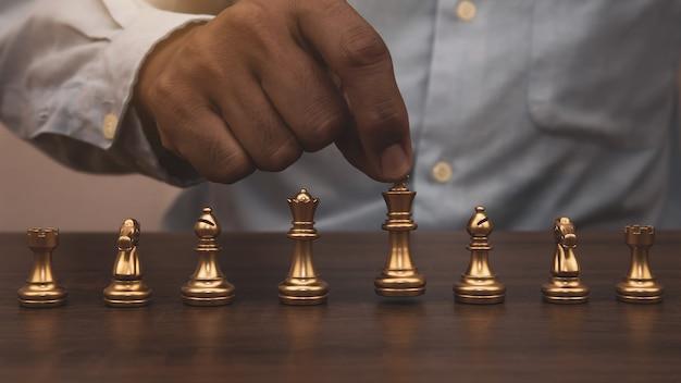 La main en gros plan choisit les échecs du roi.