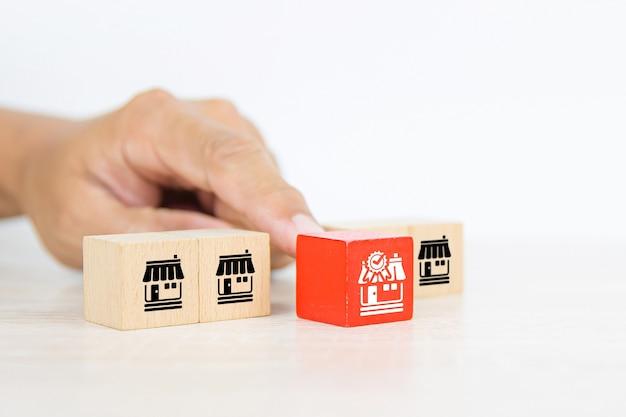 La main en gros plan choisit la pile de blocs de bois avec l'icône du magasin d'affaires de franchises.
