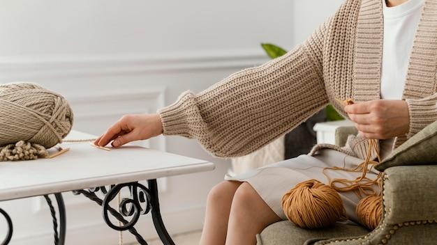 Main de gros plan, obtenir une aiguille à tricoter