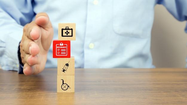 La main en gros plan protège la pile de blocs de jouets en bois avec l'icône d'assurance.