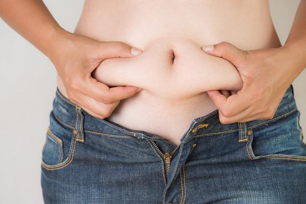 Main de grosse femme tenant sa propre graisse du ventre