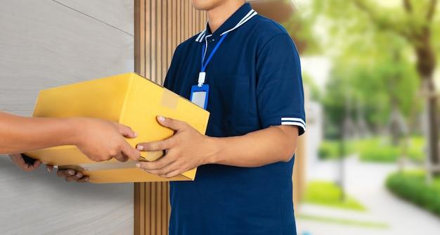 Main d'homme acceptant un colis de boîtes de services de livraison chez le livreur