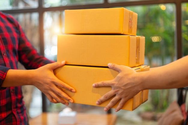 Une main d'homme acceptant une livraison de boîtes du livreur