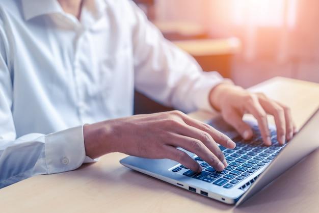 Main d'homme d'affaires à l'aide d'un ordinateur portable au bureau.