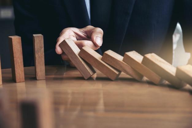 Main homme d'affaires arrêt chute bois dominos effet