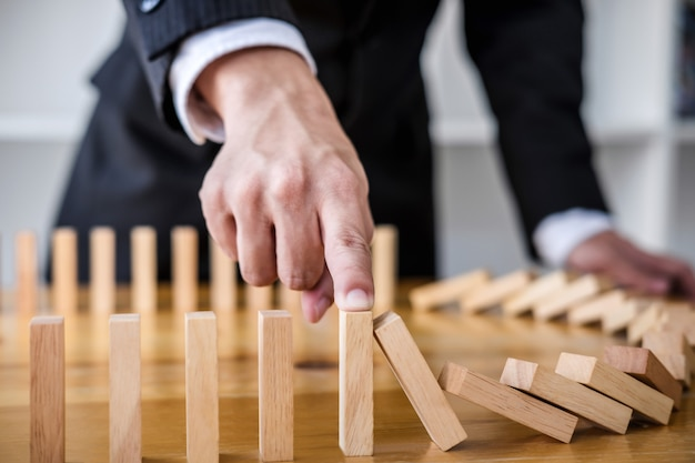 Main d'homme d'affaires arrêtant la chute des dominos en bois, renversement continu ou risque