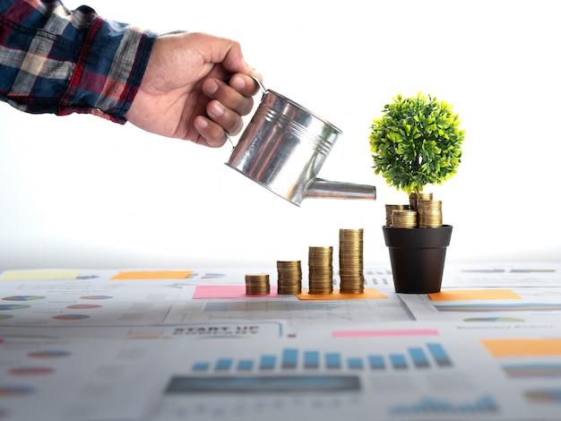 Main d'homme d'affaires arrosant une monnaie et de plus en plus d'argent
