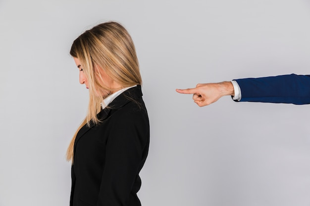 La main d'un homme d'affaires blâmant à la jeune femme d'affaires sur fond gris